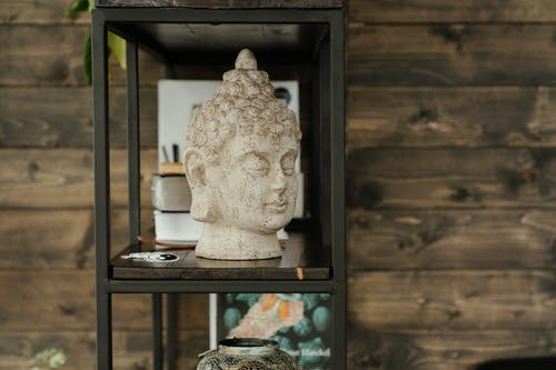 White Ceramic Figurine on Brown Wooden Shelf