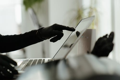Person in Black Pants and Black Leather Boots Using Macbook Pro