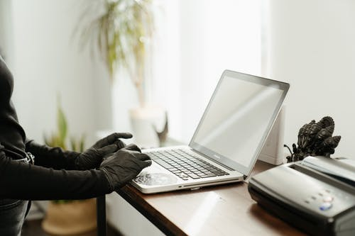 Person in Black Jacket Using Macbook Pro on Brown Wooden Table