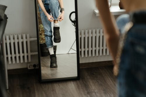 Woman in Blue Denim Shorts and Black Boots Standing on Brown Wooden Floor