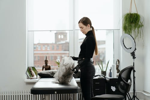 Woman in Black Long Sleeve Shirt and Black Pants Sitting on Black Chair