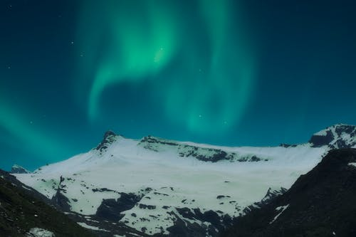 Northern Lights Above Snow Covered Mountain