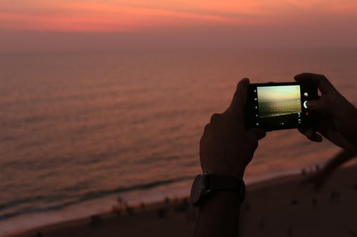 High angle of crop anonymous male traveler using smartphone while taking photo of amazing sunset over waving ocean standing above sandy beach