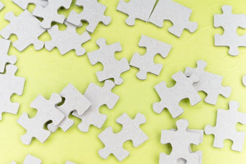 Close-Up Shot of Jigsaw Puzzle Pieces on a Yellow Surface