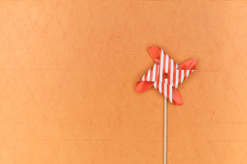 Red and White Pinwheel on Brown Surface