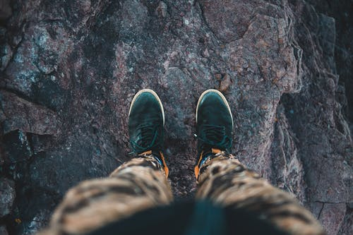 From above of crop anonymous anonymous traveler in stylish sneakers standing on top of rough rocky cliff and admiring view
