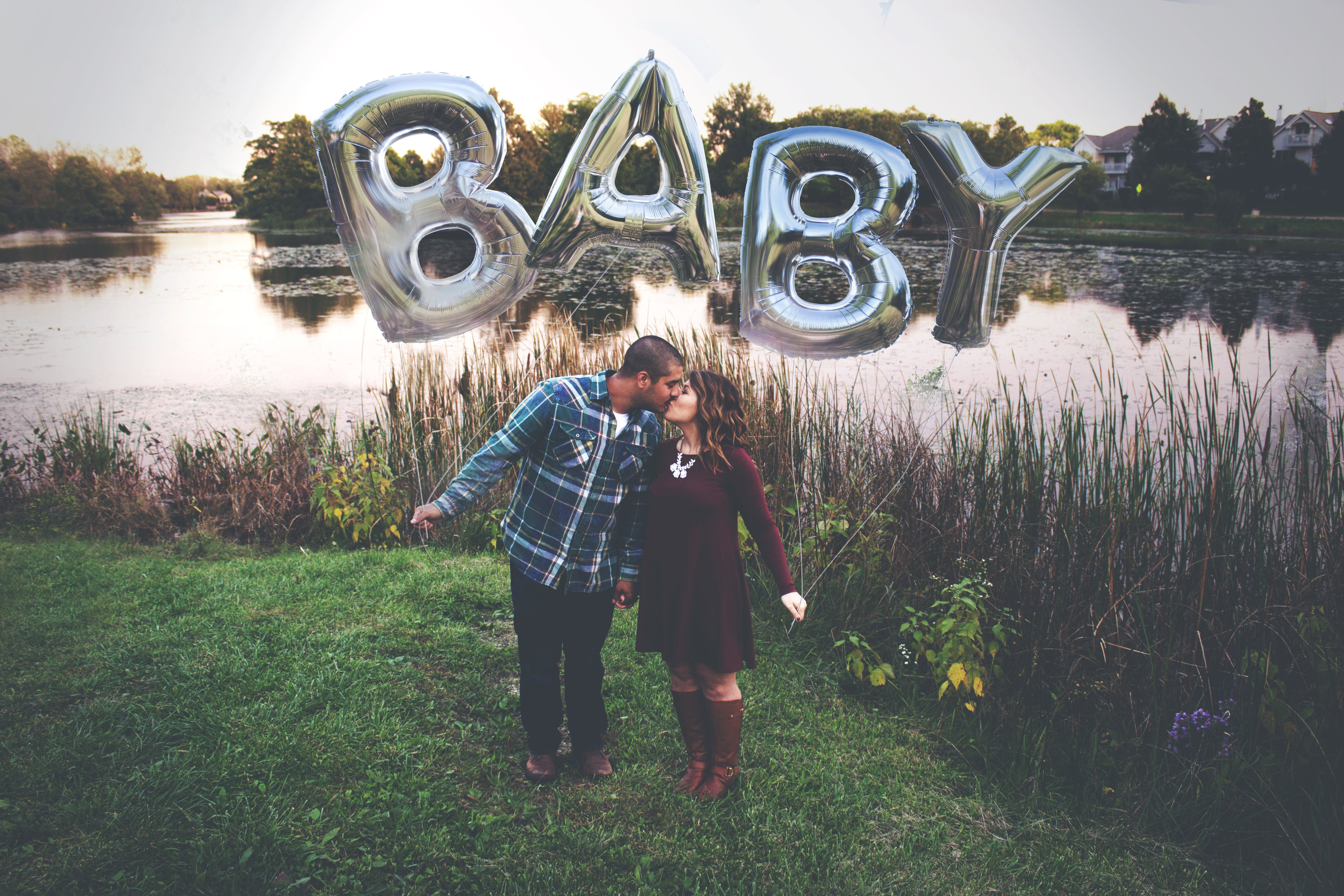 Couple Kissing While Holding Gray Baby Mylar Balloons