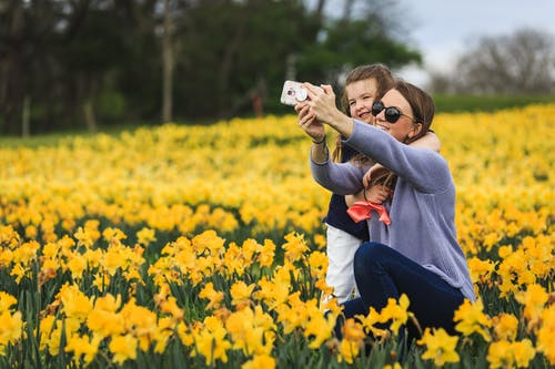 Woman in Gray Hoodie Carrying Baby in Orange Jacket on Yellow Flower Field