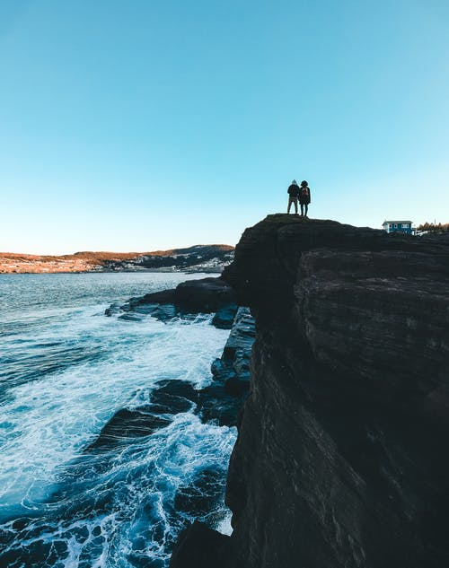 Photo Of People Standing On Cliff Edge