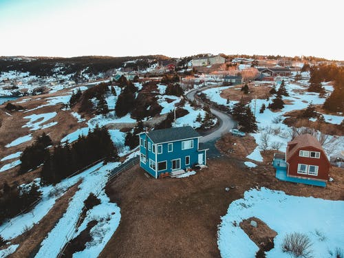 Picturesque drone view of village terrain with colorful houses and conifers covered with snow