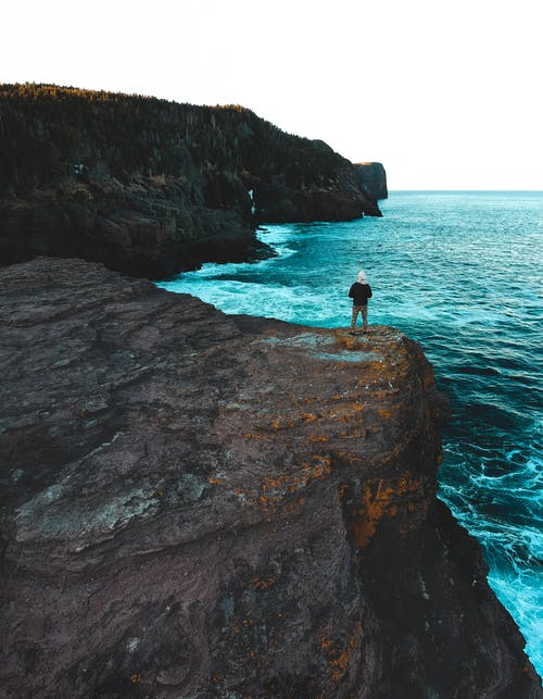 Photo Of Person Standing On Cliff Edge