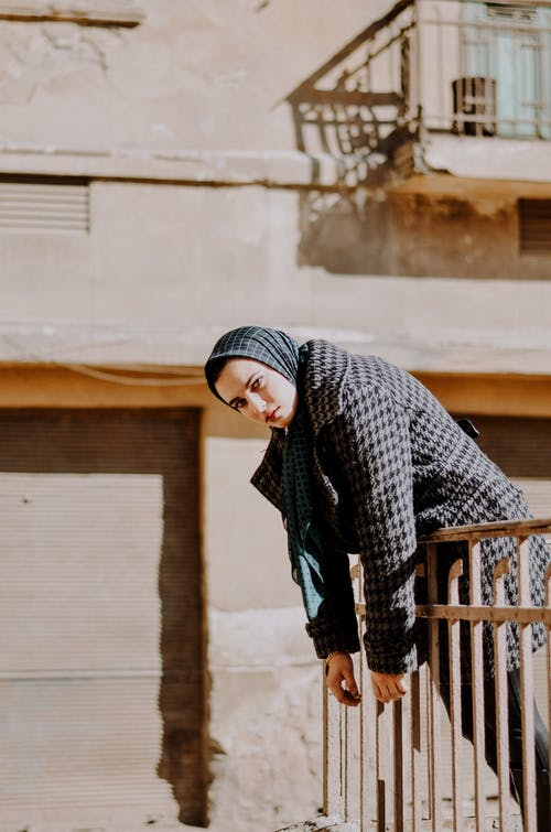 Woman in Black and White Hijab Standing Beside Brown Wooden Fence