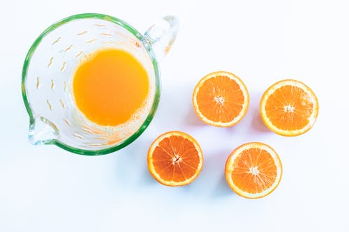 Photo Of Sliced Orange Beside Glass Pitcher