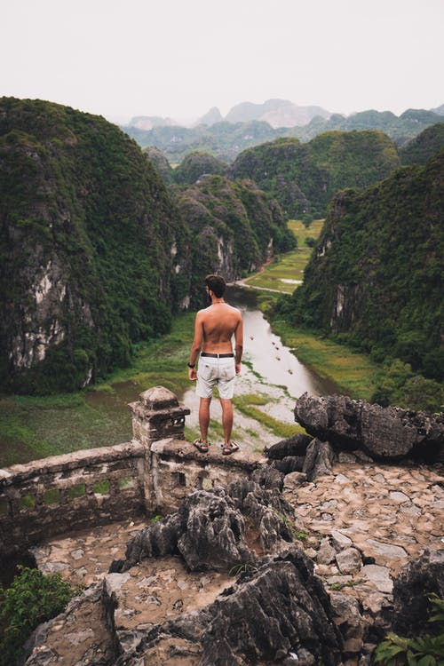 A Topless Man Standing on a Dilapidated Stone Railings Overlooking the Mountain Scenery