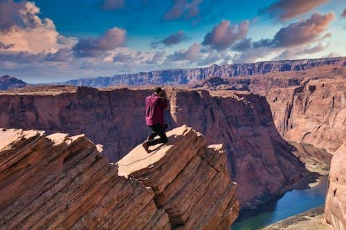 Man in Black Jacket Sitting on Brown Rock Formation