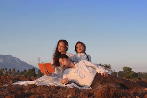 2 Women Sitting on Brown Rock