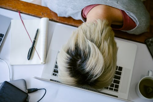 Exhausted woman with head on keyboard