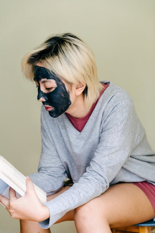 Woman with facial mask reading book