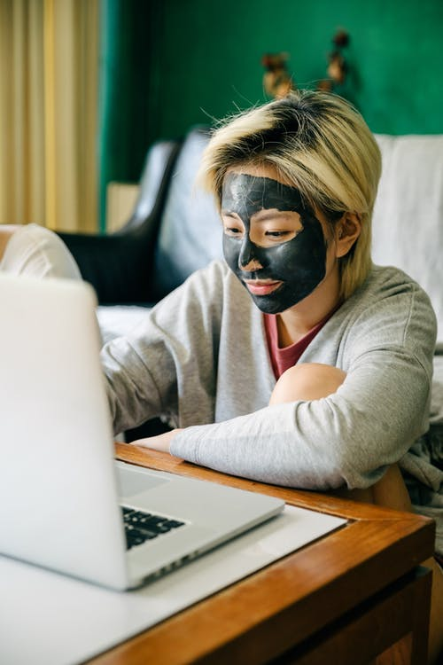 Young woman with facial mask using laptop