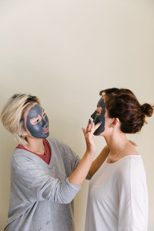 Young women applying black facial mud mask on beige background