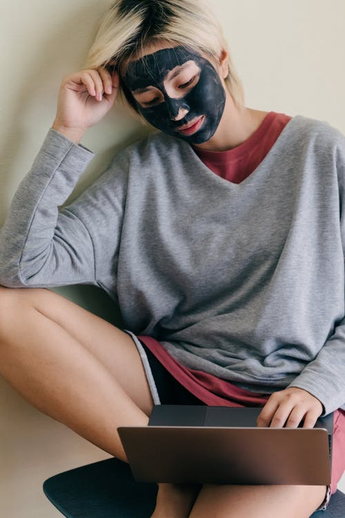 Young woman with cosmetic facial mask sitting on chair while using laptop at home