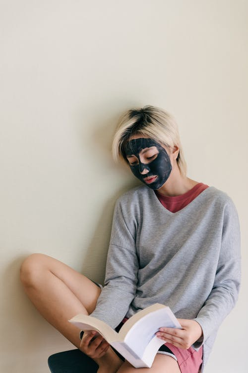 Concentrated young Asian female in casual wear with black cosmetic facial mask sitting relaxed on chair while reading book at home