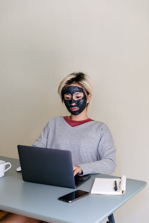 From above of concentrated young ethnic female student in casual outfit with black clay face mask using laptop while sitting at table on beige background