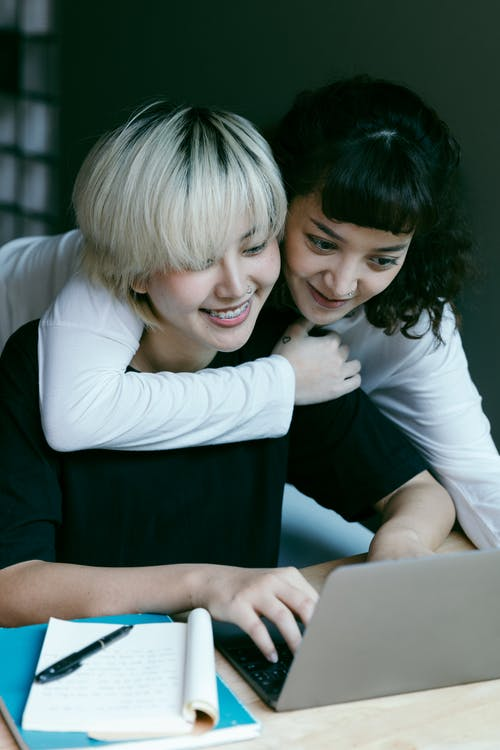 Happy women using laptop in workspace