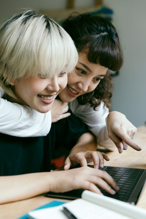Positive smiling Asian girlfriends hugging and looking at laptop screen while working on homework together at table with opened notebook