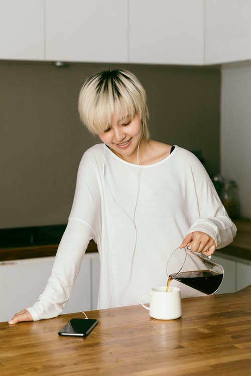 Happy woman in earphones pouring freshly brewed coffee into cup