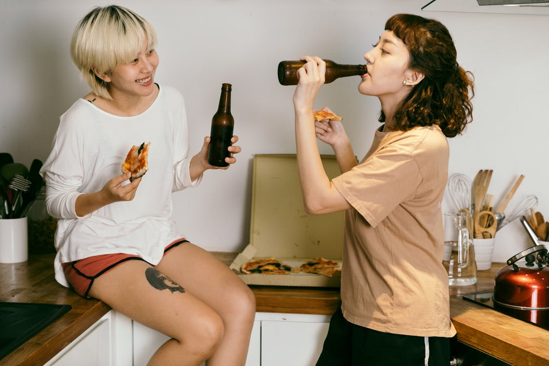 Happy tattooed blond lady eating pizza while looking at female friend in casual wear drinking beverage from bottle near kitchen utensils in apartment