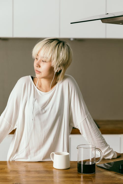 Dreamy young female in casual wear and earphones listening to music in morning while standing near wooden table with glass jug of coffee and white cup and looking away