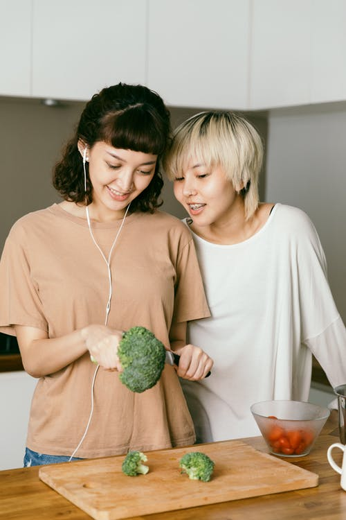 Woman in earphones cutting broccoli while standing near happy friend