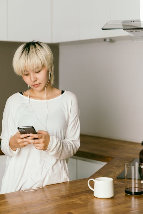 Thoughtful woman in earbuds chatting on smartphone in kitchen