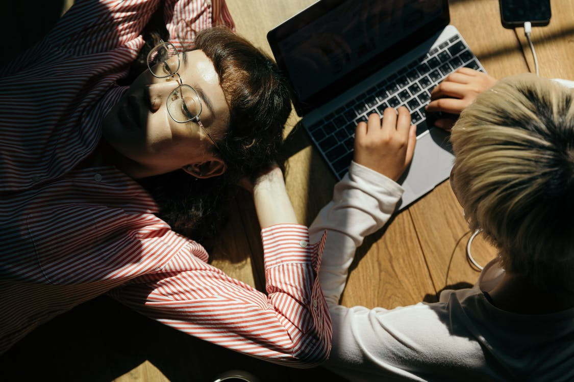 From above of lady in eyewear lying on wooden floor near anonymous female remote worker typing on netbook and listening to music in earphones form smartphone
