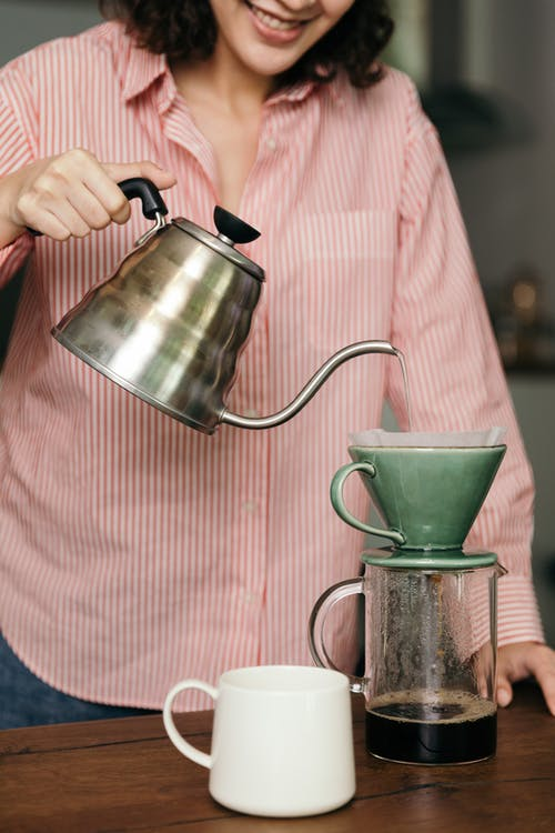 Crop unrecognizable woman with kettle preparing fresh coffee in kitchen