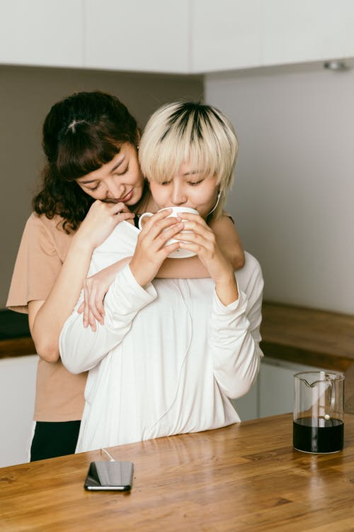 Woman embracing female friend in earbuds drinking coffee in kitchen