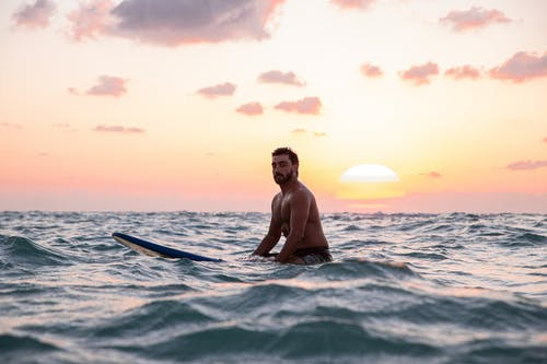 Photo Of Man Riding A Surf Board