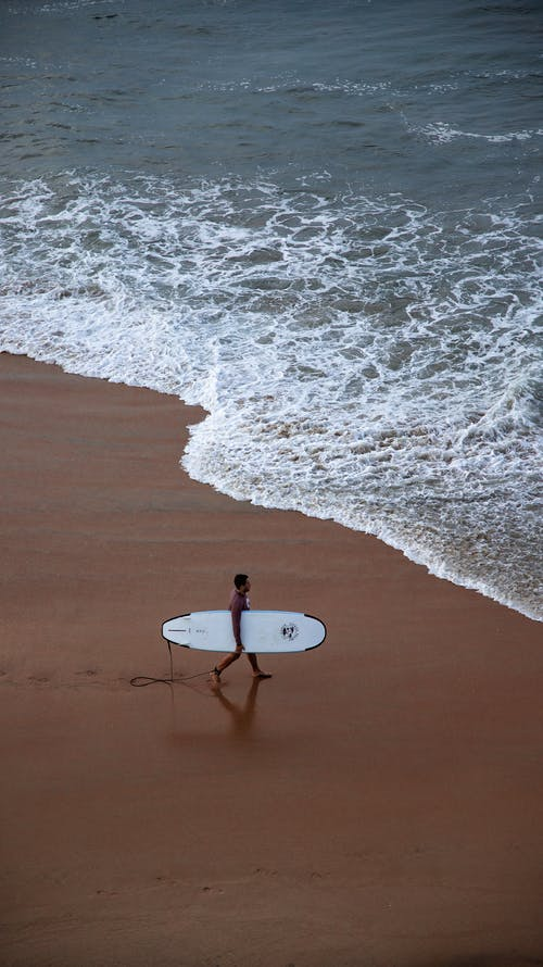 Photo Of Person Carrying Surf Board