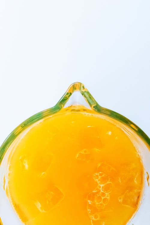 Overhead view of glass jar of orange juice with green spout and edging on white background