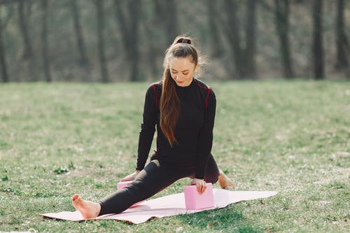 Flexible young women performing yoga exercise in park