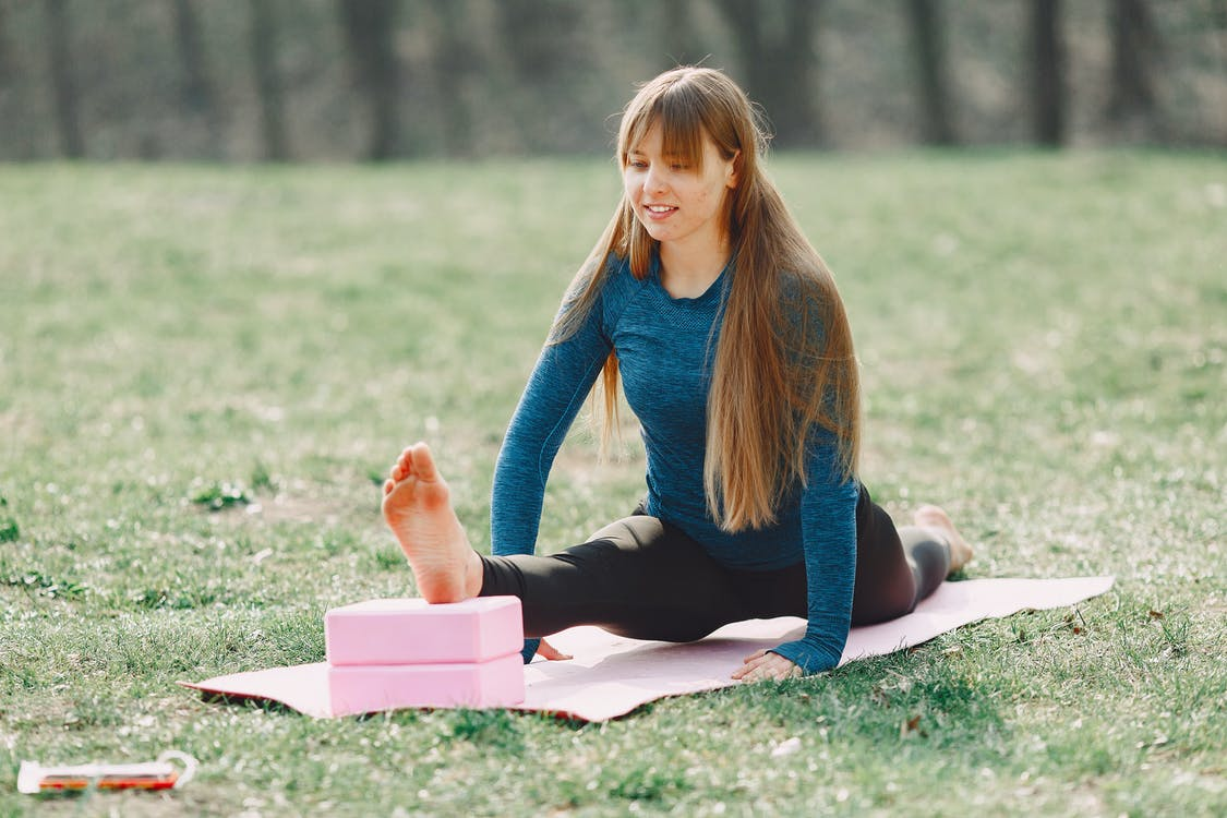 Positive young woman doing yoga with blocks on lawn