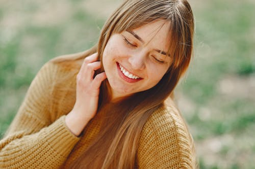 Crop happy young female with long hair wearing stylish sweater smiling with closed eyes while touching hair against background of blurred green field