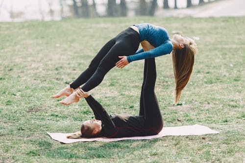 Determine women doing acro yoga exercise together