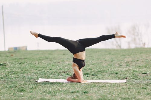 Young barefoot woman performing yoga asana on green field