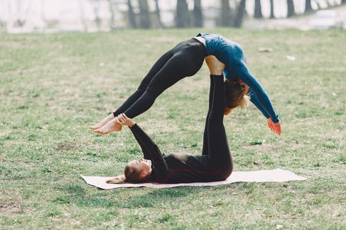 Slim young barefoot sportswomen in sportswear doing together acrobatic yoga exercise on mat during training on green field adhering to healthy lifestyle