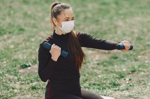 Slim female athlete in sports clothes and sterile mask using dumbbells during workout on grass and looking away in daylight during COVID 19 pandemic