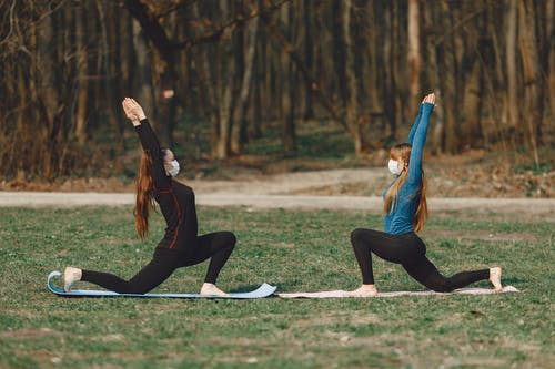 Sportive girlfriends in face masks standing in Crescent Lunge pose