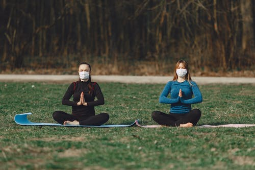 Tranquil girlfriends in face masks sitting in Namaste pose