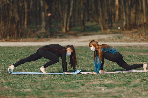Girlfriends in face masks doing Lunge pose while practicing yoga